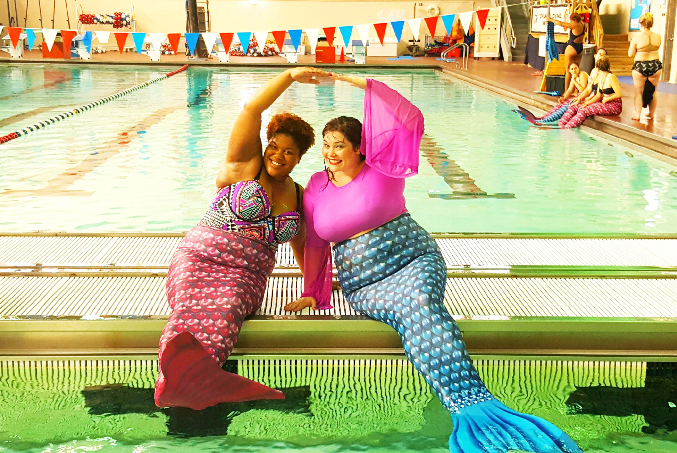Two Plus Size Bloggers pose in mermaid tails at an Aquamermaid class